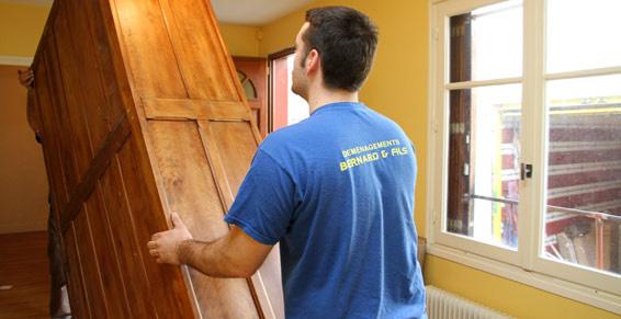 Déménageurs dans une maison en train de soulever un meuble lourd