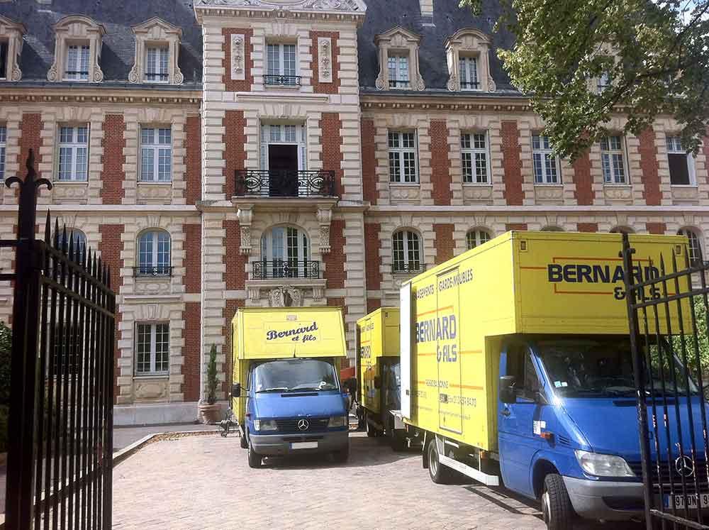 Camions de l'entreprise de déménagement Bernard et Fils jaune et bleu lors d'un déménagement dans la cours d'une propriété